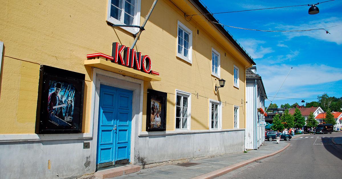 Innganspartiet til Drøbak kino fra Storgata. Blå dør på gul mur og filmplakater på utsiden.
